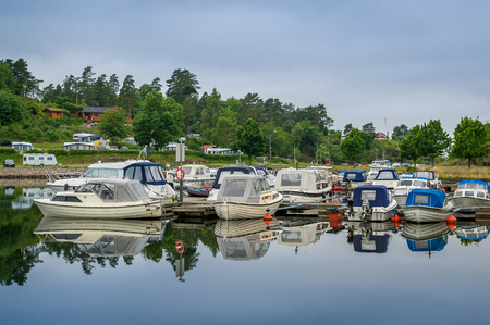Small recreational motor boats at Falkensten village camping. Norway.