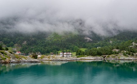 Houses of norwegian village at fjords shores . Clouds are hiding mountain peaks above the town. Lysefjord, Norway.