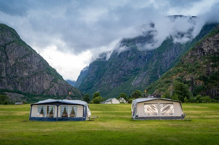 Camping field with camper tents under the rocky mountains of norwegian fjord. Eidfjord, Hordaland, Norway