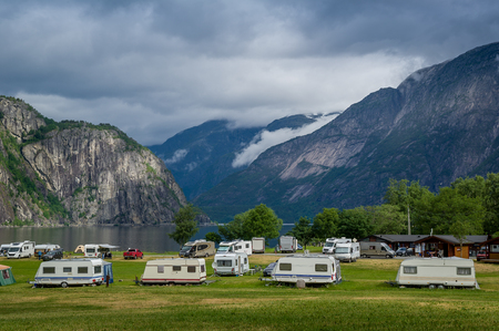 Camping field with campers at beautiful north sea fjord with mountains in clouds at the background. Eidfjord, Hordaland, Norway Stock Photo