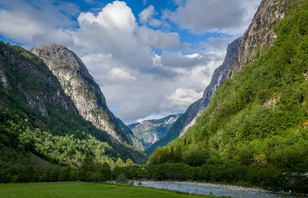 Mountain river and steep rocky mountains at evening light. Travel Norway.