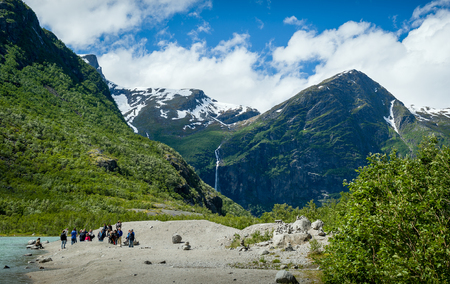 and hiking path: Group of tourists at the lake shore, popular hiking path finish and Briksdalsbreen glacier viewing point. Briksdal, Norway. Stock Photo