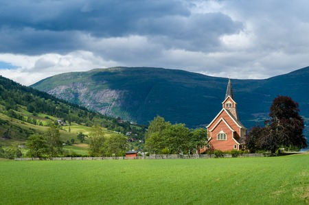 Small church and road in norwegian fields. Rural country landscapes of Norway.