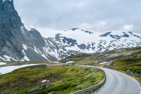 Mountain road at Dalsnibba plateau and snowy peaks ahead. Geiranger, Norway