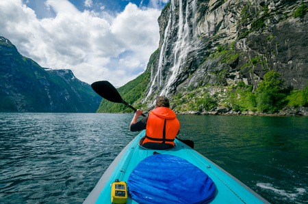 Woman kayaker in bright orange life vest on her trip in Geiranger fjord waters. Geirngerfjord, Norway.