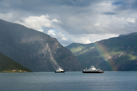 Fjord ferries and rainbow landscape. Stock Photo