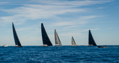 Racing sailing yachts with black sails in the mediterranean sea. Saint-Tropez regatta, France.