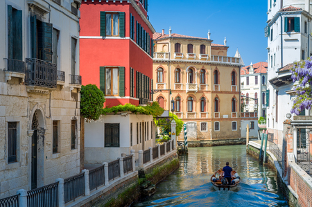 Venice traditional view with historic buildings and small boat the channel street. Veneto, Italy.