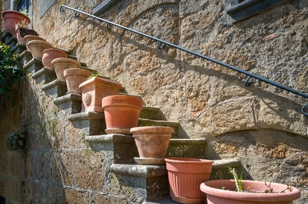 Flower pots at the steps of Civita di Bagnoregio old house. Tuscany, Italy.