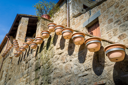 Medieval wall decorated with many flower pots. Civita di Bagnoregio, Tuscany, Italy. Stock Photo - 114302139