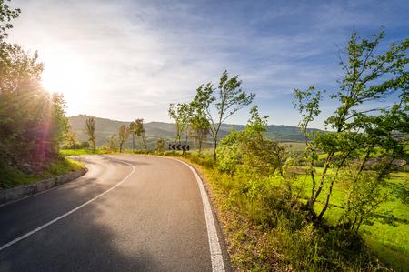 Curved road with sunset sunshine atToscana Val dOrcia fields. Tuscany region, Italy. Stock Photo