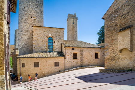 Tourists walking at San Gimignano - mediewal town of towers. Toscana, Italy. Stock Photo