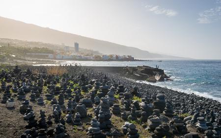 Sunset landscape of ocean shore and zen stone pyramids field at Puerto de la Cruz. Tenerife island, Spain.