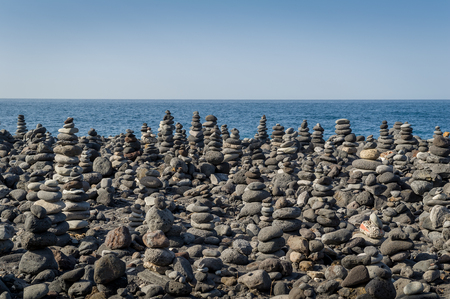 Zen stones. Stone pyramids field at ocean coast. Puerto de la Cruz. Tenerife island, Spain. Stock Photo