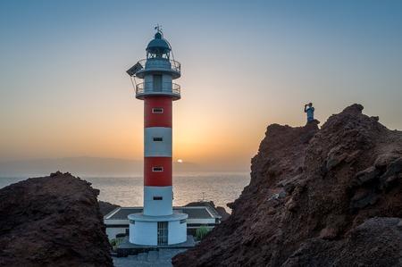 Tourist is taking photos of Punta de Teno Lighthouse sunset landscape. Popular touristic destination at Tenerife island. Canary islands, Spain. Stock Photo