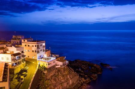 Buildings on the rocks and Atlantic ocean night scene. Puerto de Santiago. Tenerife islans, Canarias, Spain Stock Photo