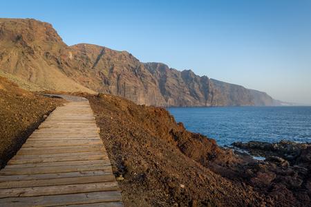 Wooden walking path at Punta de Tena. Los Gigantes rocks and ocean view at sunset light. Tenerife, Canarias, Spain. Stock Photo
