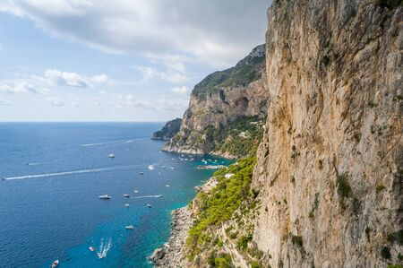 Rocks and cliffs of Capri island. Viewpoint to the sea bay with small locals boats and perfect climbing walls. Capri, Italy.