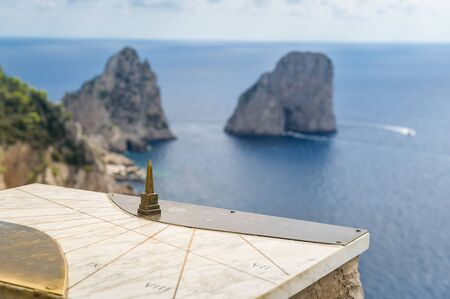 Capri island viewpoint with old coordinate map and blurred Faraglioni rocks at the background. Amalfi coast, Italy.