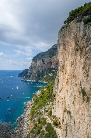 Vertical photo of rocks and cliffs of Capri island. Viewpoint to the sea bay with small locals boats and perfect climbing walls. Capri, Italy. 版權商用圖片