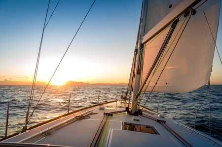 Chasing the sun at sailing yacht. Deck and sails of sailoat pointing to the sunrise. Mediterranean sea, Italy. Stock Photo