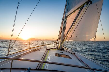 Sailing yacht navigationg to the sun rising on the horizon.. Mediterranean sea, Italy.