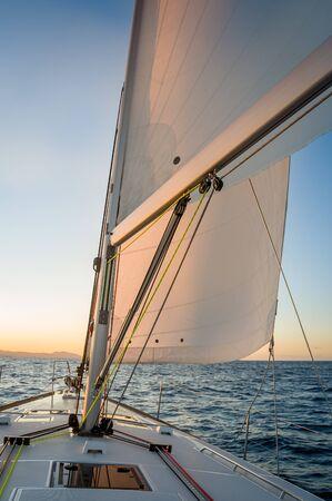 Der Sonne auf der Segelyacht nachjagen. Deck und Segel von Segelbooten, die auf den Sonnenaufgang zeigen. Mittelmeer, Italien. Standard-Bild