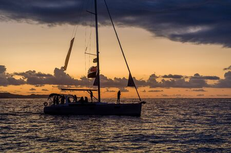 Sailing yacht silhoette at bright orange sunset background. Sailing at Amalfi coast, Italy.