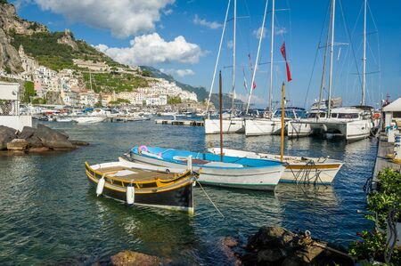 Traditional boats and modern yachts docked at Amalfi marina, Italy. 版權商用圖片