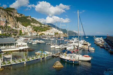 Amalfi harbor with lots of different type boats and town view. Italy.