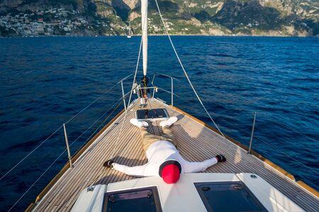 Homme relaxant au pont en teck du voilier de luxe. Côte amalfitaine, Italie.