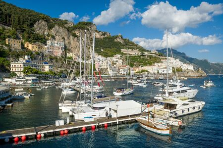 Sailing yachts and catamarans at Amalfi port. Sailing cruise route spot in Italy.