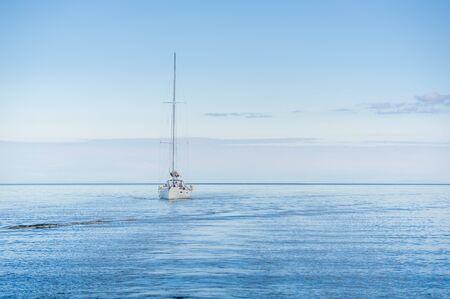 Yacht sailing alone in the flat sea of Hebrides islands. Isle of Arran, Scotland.