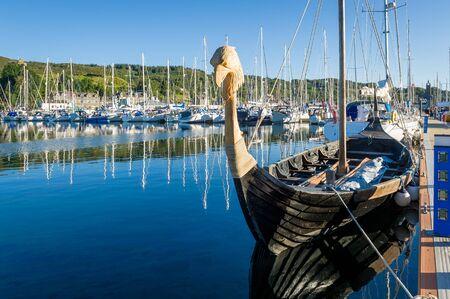 Old drakkar - historic vikings boat at Tarbert marina. Hebrides, Scotland.