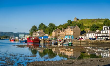 Tarbert pier with fishermans boats and ferry. Low tide water and evening light. Scotland.