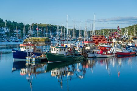 Beautiful calm day in Tarbert harbor. Colorful loals boats and water reflections. Inner Hebrides, Scotland.