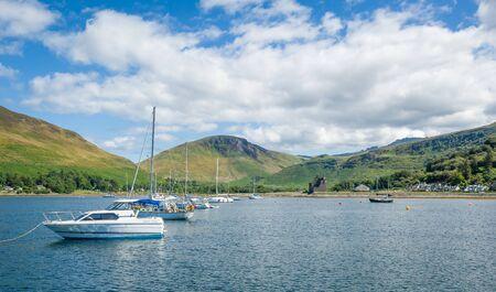Lochranza bay with boats at anchor. Arran island, sailing trip in Scotland.