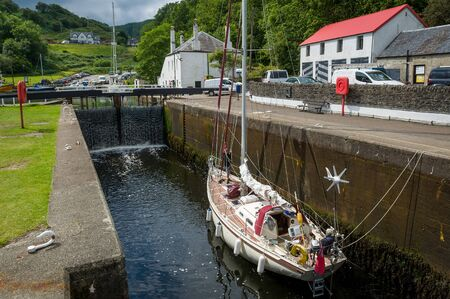 Sailing boats passes gates of Crinan canal. Scotland sailing cruise. Stok Fotoğraf