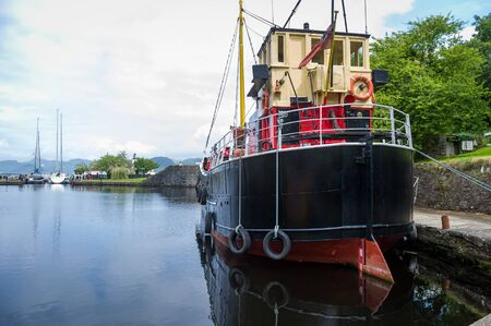 Old steel ship with black hull docked at Crinan channel, Scotland Stok Fotoğraf
