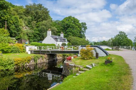 Beauty of Crinan canal - scenic water way with gates and bridges. Summer in Scotland.