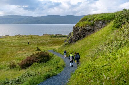 Tourists walking at the eastern cape of Mull island, Scotland