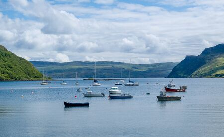 Portree harbor with small boats staying at anchors, Island of Skye, Hebrides archipelago, Scotland.