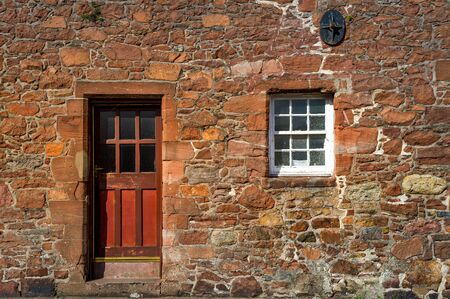 Red medieval wall with wooden door and fortified window. Campbeltown street, Scotland.