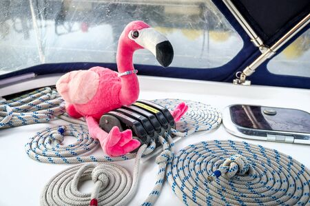 Pink flamingo toy and sailing yacht ropes perfectly coiled near it's clamps. Largs, Scotland.