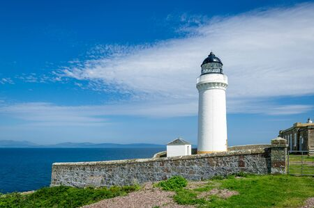 White lighthouse tower and stone fence. Davaar island, Scotland