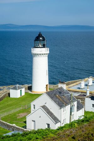 Davaar island white lighthouse and cottadges vertical photo. Campbeltown, Scotland Standard-Bild