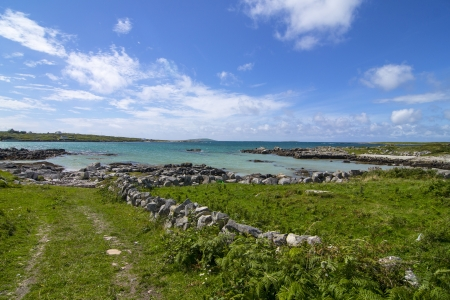 Landscape in Connemara, a turquoise beach and a beautiful green field photo