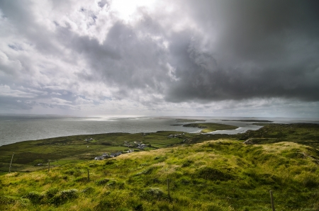 beautiful landscape with the green fields, the sea and clouds in Connemara, Ireland photo