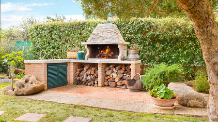 stone fireplace: External Wood oven with burning fire and firewood Stock Photo