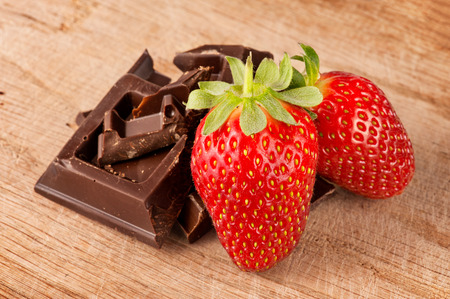 Strawberries with chocolate bar in pieces